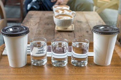 Coffee cup set which consist of glassed of water and ice coffee in paper cup