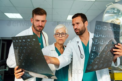 Group of doctor looking at ct scan at hospital to make diagnosis