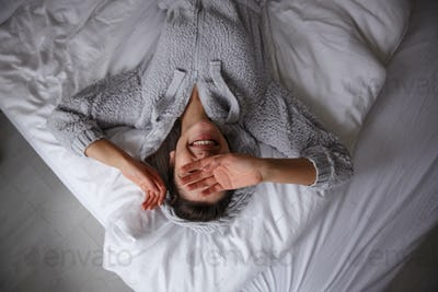 Happy young brunette lady basking in her bed in early morning, lying on white linens
