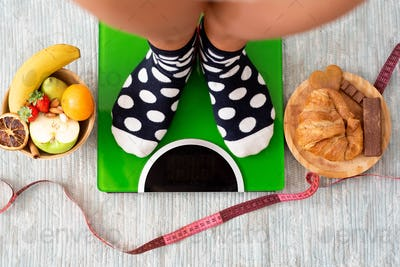close up and portrait of legs ad feet weighing on a weight scale to see if she has lose weight
