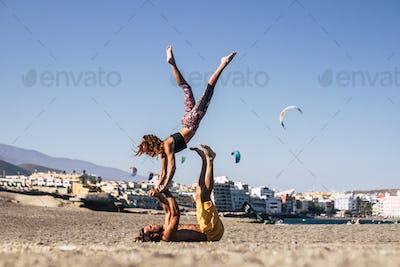 couple of two adults and people together at the beach training together on the sand