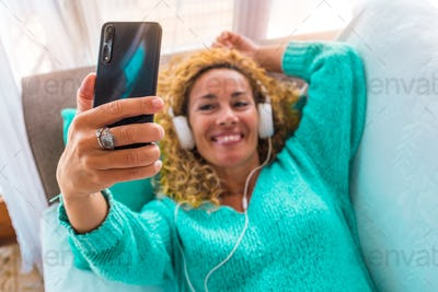 close up of hand of woman holding a phone and taking a selfie of her listening music