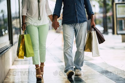 close up of legs of two adults walking on a mall with five shopping bags with clothes on it