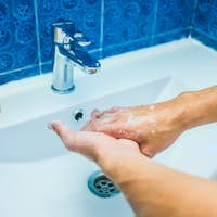 close up of man or woman at home in the bathroom preventing coronavirus or covid-19