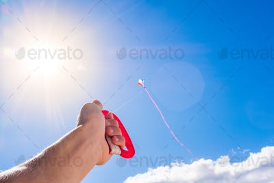close up and portraitof hand holding a flying kite in the blue sky - freedom lifestyle and concept