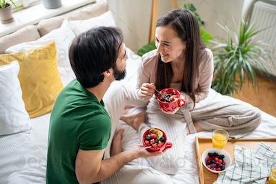 Young couple in love eating breakfast on bed indoors at home.