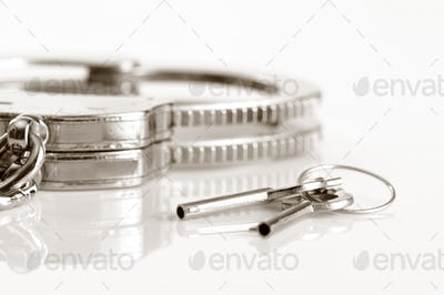 Metal handcuffs and keys isolated over white background