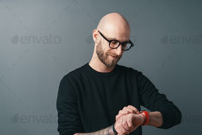 Smiling handsome bearded man with glasses looking at his smart watch