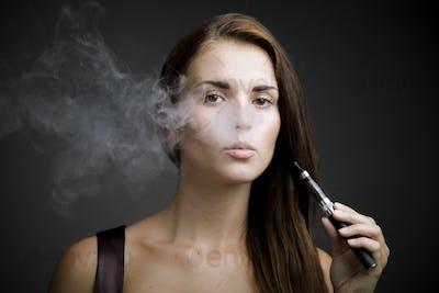 Elegant woman smoking e-cigarette with smoke