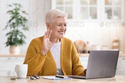 Happy old lady having video conversation with family