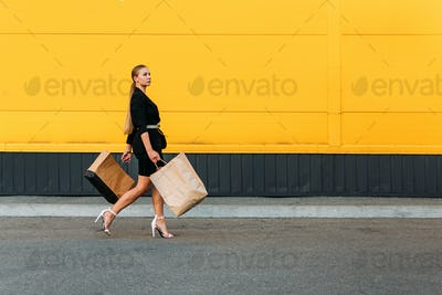 Shopping, sale concept. Stylish fashionable woman walking and holding shopping bags on yellow wall