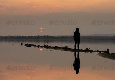 Unrecognised person standing and enjoying the sunset at a lake. Larnaca Cyprus