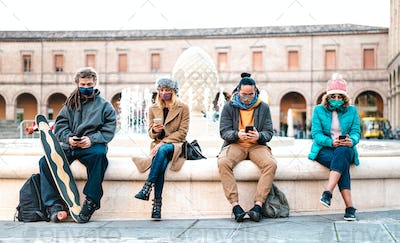 Millenial friends watching video on smart phones with face mask