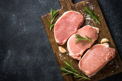 Fresh pork steaks on cutting board with ingredients for cooking.