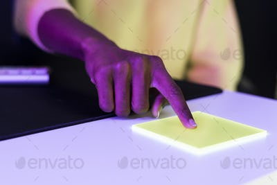Index finger pressing on yellow transparent plate smart technology