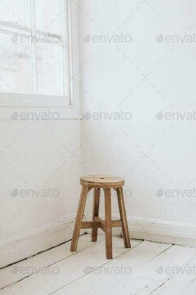 Wooden stool in the corner of a room