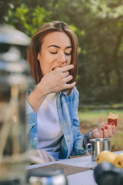 Woman eating cake in breakfast into the forest