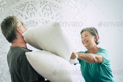 Old and youthful people mature retired man and woman play at home at war pillow in the bedroom