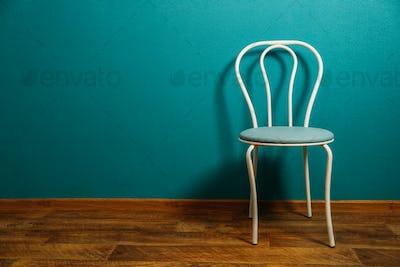 Minimalism in design, renovation. Minimalist Apartment Decor. White chair against empty blue wall