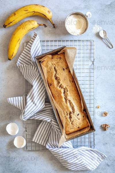 Flat lay of a banana bread with banana, flour and walnuts on a white background