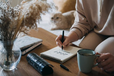 2021 goals, new year resolution, planning. Woman writing in Notebook