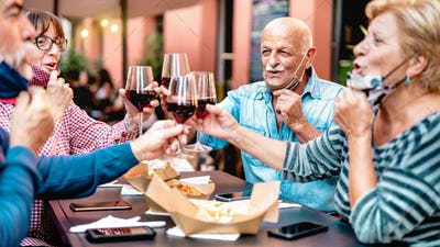 Senior friends toasting wine at restaurant bar wearing opened face mask