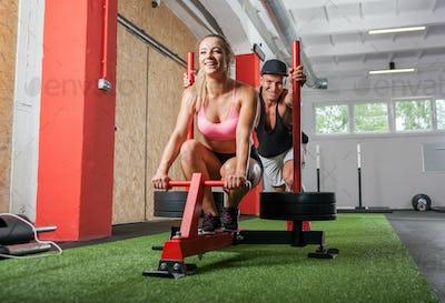 Muscular man pushing sled, fun in gym during exercise