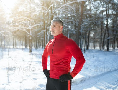 Happy senior man in warm sports clothes taking break after jogging at snowy winter forest. Seasonal