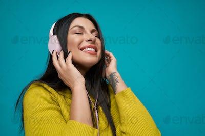 Brunette in headphones listening music and smiling
