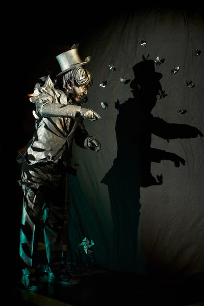 Male mime actor showing figure with his shadow on black wall