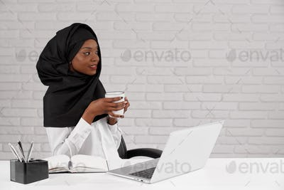 Charming african muslim woman at table in office