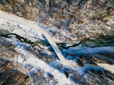 Curvy Road Brodge over Frozen River. Winter Landscape in Mountains.