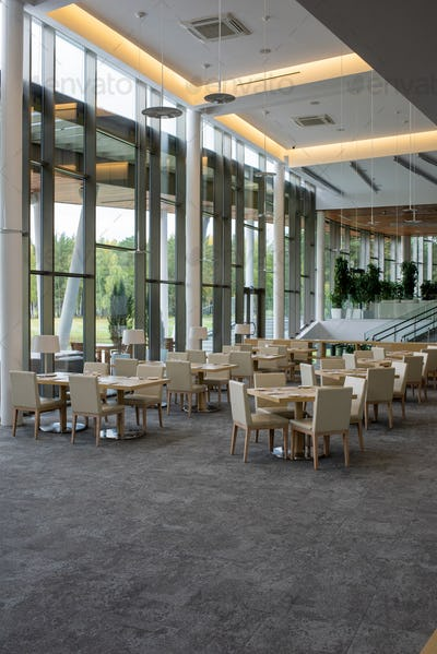 Interior of five star restaurant inside modern business center with many tables