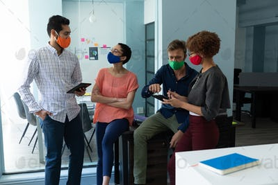 Diverse group of work colleagues wearing masks talking together