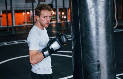 Young man in white shirt and boxing protective gloves doing exercises in gym with pushing bag