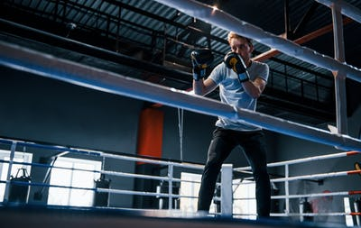 Young man in white shirt and protective gloves doing exercises in boxing ring