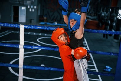 Portrait of two young boys in protective gloves celebrating victory on boxing ring
