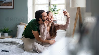Young couple taking selfie on bed indoors at home.
