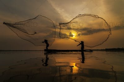 Silhouette of asia traditional fisherman in action when fishing at sunrise
