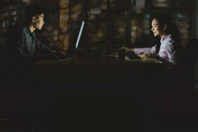 Asian business woman and business man working hard late together with technology computer in office