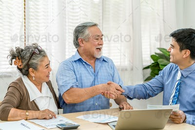 Insurance agency manager handshake with Asian couple grandparent in happy feeling after deal