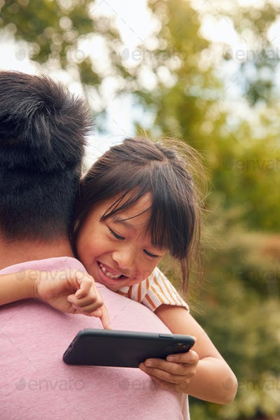 Asian Father Cuddling Daughter In Garden As Girl Looks Over His Shoulder At Mobile Phone