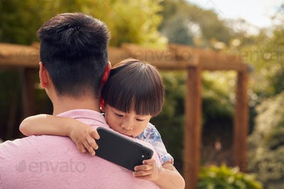 Asian Father Cuddling Son In Garden As Boy Looks Over His Shoulder At Mobile Phone