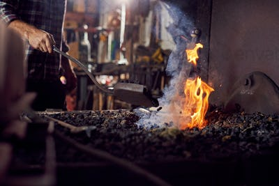 Male Blacksmith Adding Coal Fuel To Wood Kindling To Start Blaze In Forge