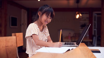 Young Asian Girl Home Schooling Working At Table Using Laptop