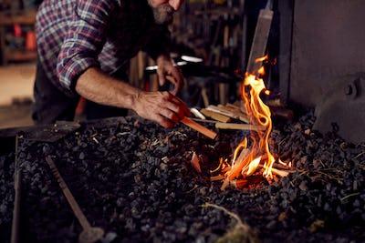Male Blacksmith Lighting Wood Kindling To Start Blaze In Forge