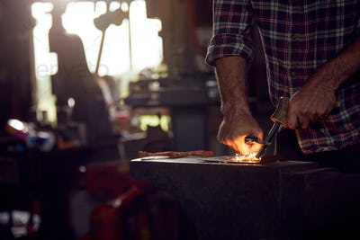 Close Up Of Male Blacksmith Lighting Wood Shavings With Firesteel On Anvil To Light Forge