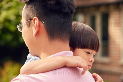 Loving Asian Father Cuddling Son In Garden As Boy Looks Over His Shoulder