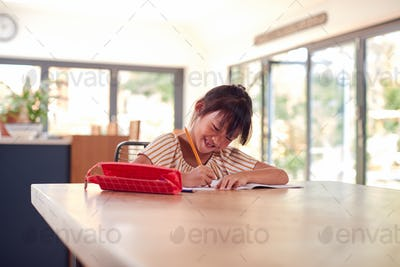 Young Asian Girl Home Schooling Working At Table In Kitchen Writing In Book