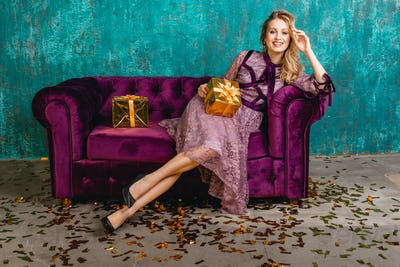 stylish woman in party dress sitting on sofa with presents on christmas